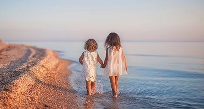 Twee kinderen wandelen langs het strand