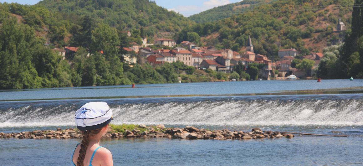 Persoon met Le Boat hoed kijkt over de barrage